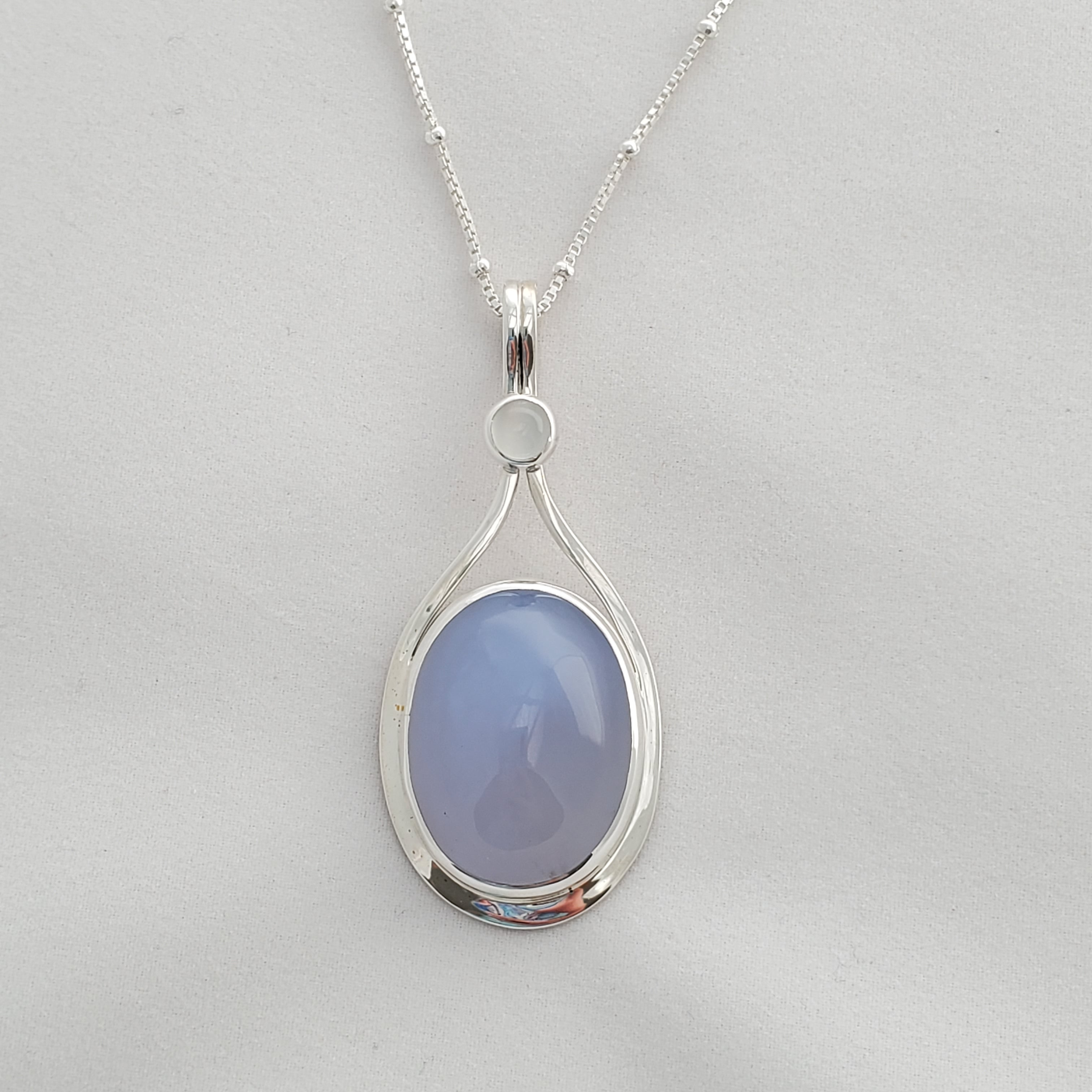 Teardrop silver border with oval lavender Chalcedony gemstone inside, accented with a small round moonstone at the top.