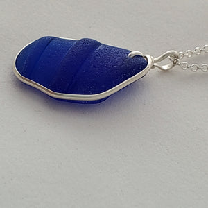 Side view of ridged cobalt blue sea glass necklace with sterling silver wire wrapping around ouside edge.