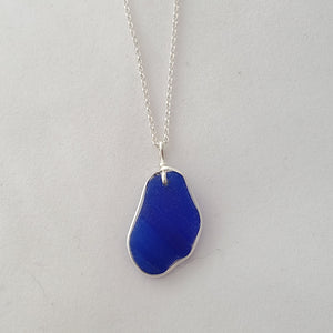 Front view of ridged cobalt blue sea glass necklace with sterling silver wire wrapping around ouside edge.