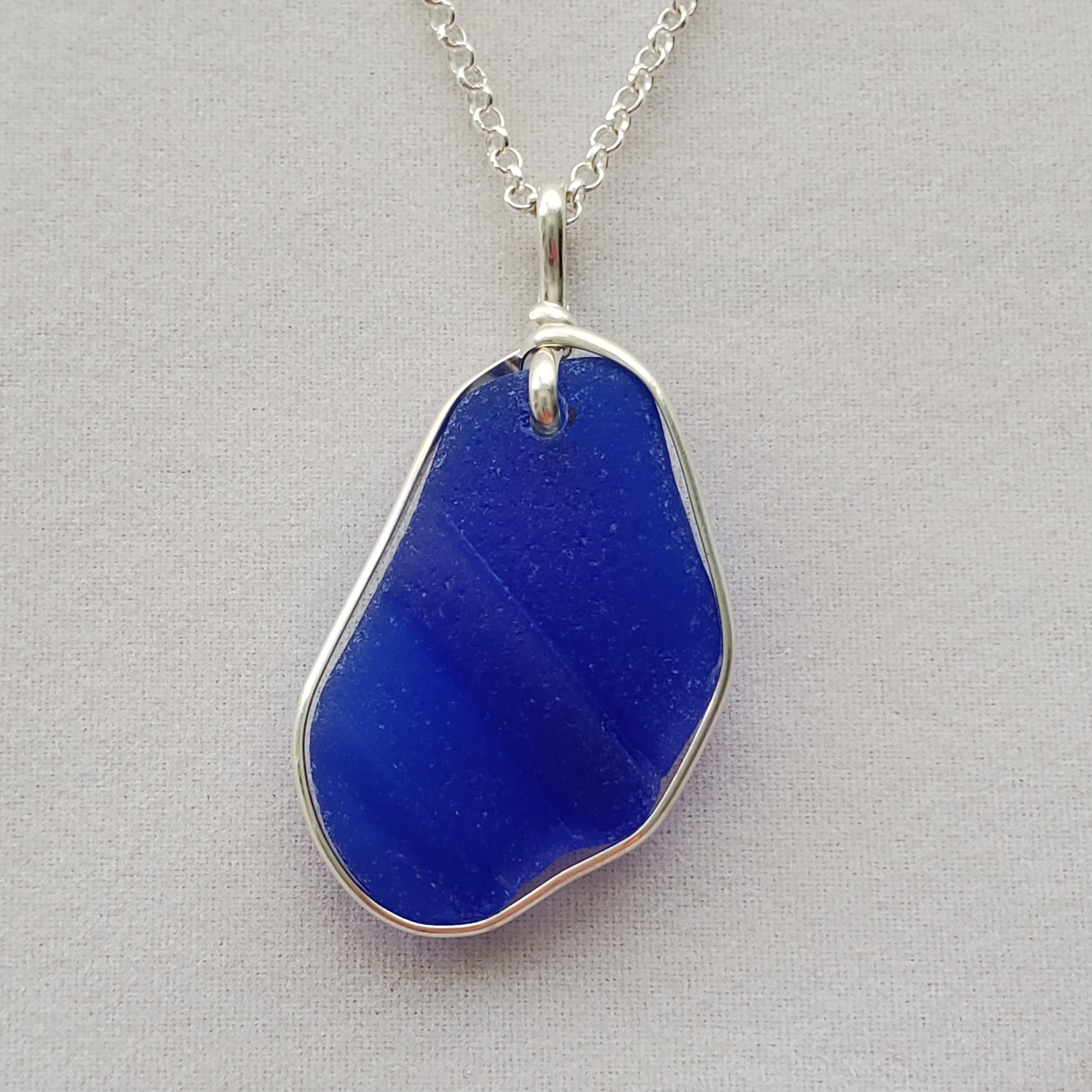 Close-up of ridged cobalt blue sea glass necklace with sterling silver wire wrapping around ouside edge.