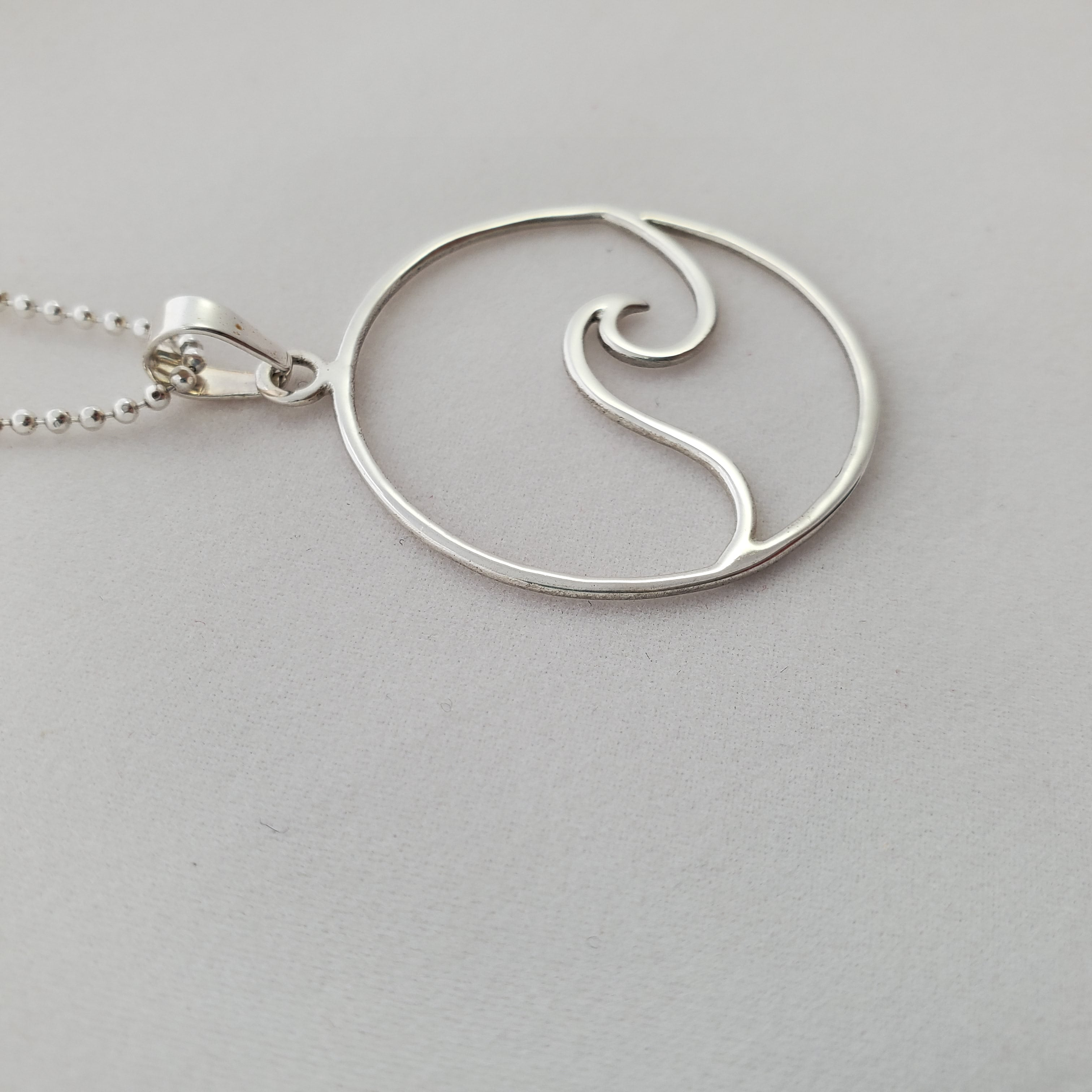 Side view of circle with wave necklace.