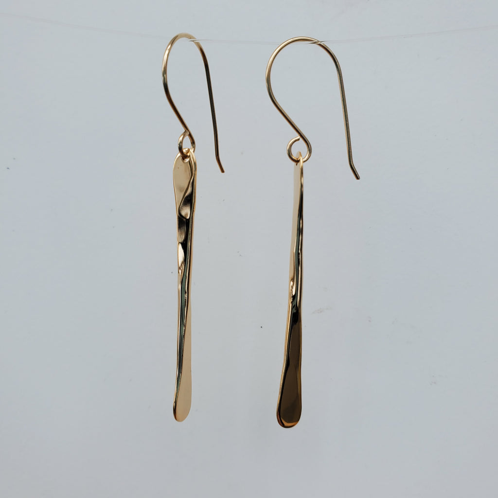 Front and three quarter view of hammered gold-filled rounded bar earrings with semi-twist.