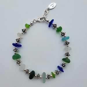 Bracelet featuring green, blue, agua, and white seaglass with round and decorative sterling silver beads and lobster clasp displayed in clasped circle.