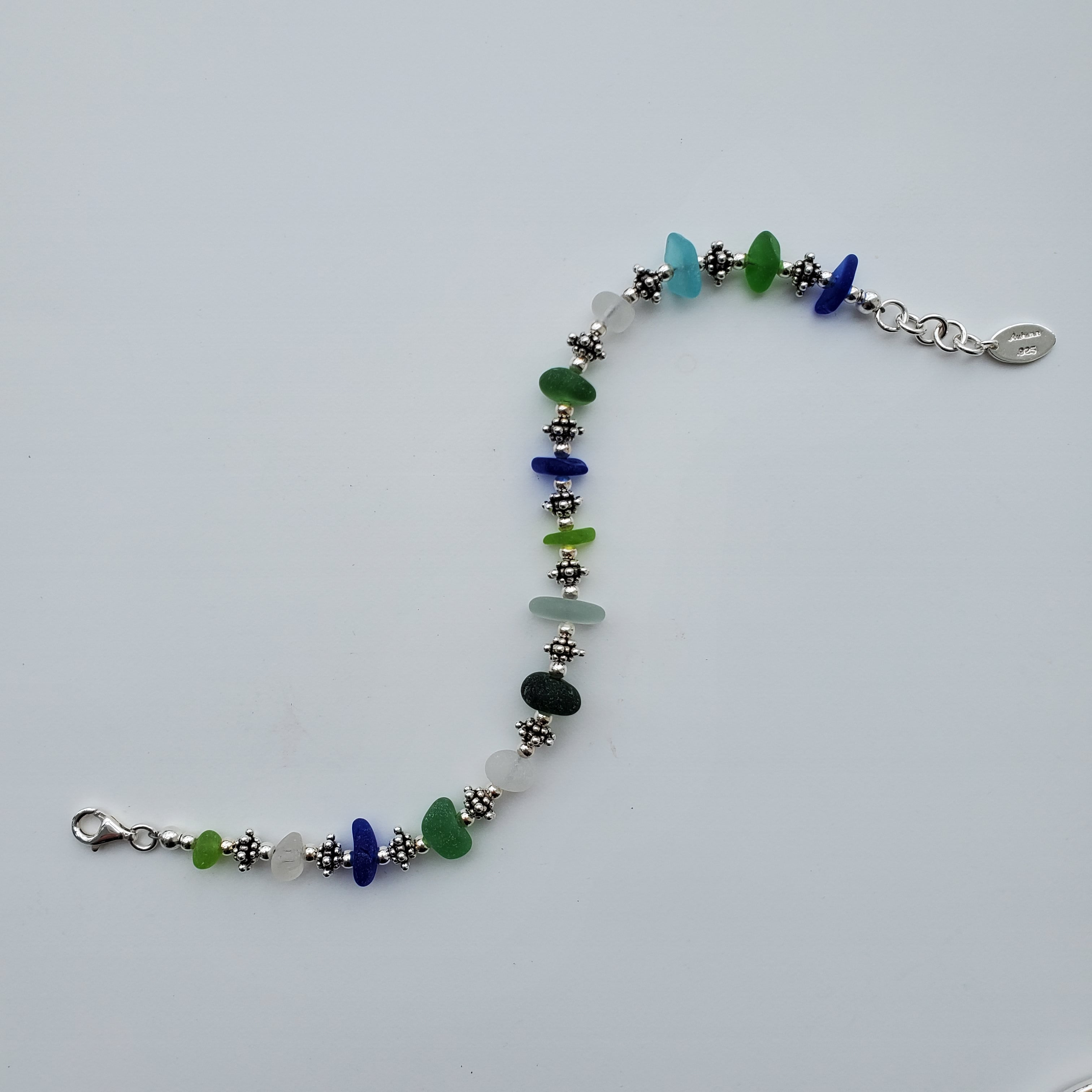 Seaglass with round and decorative sterling silver beaded bracelet displayed in unclasped S-curve.