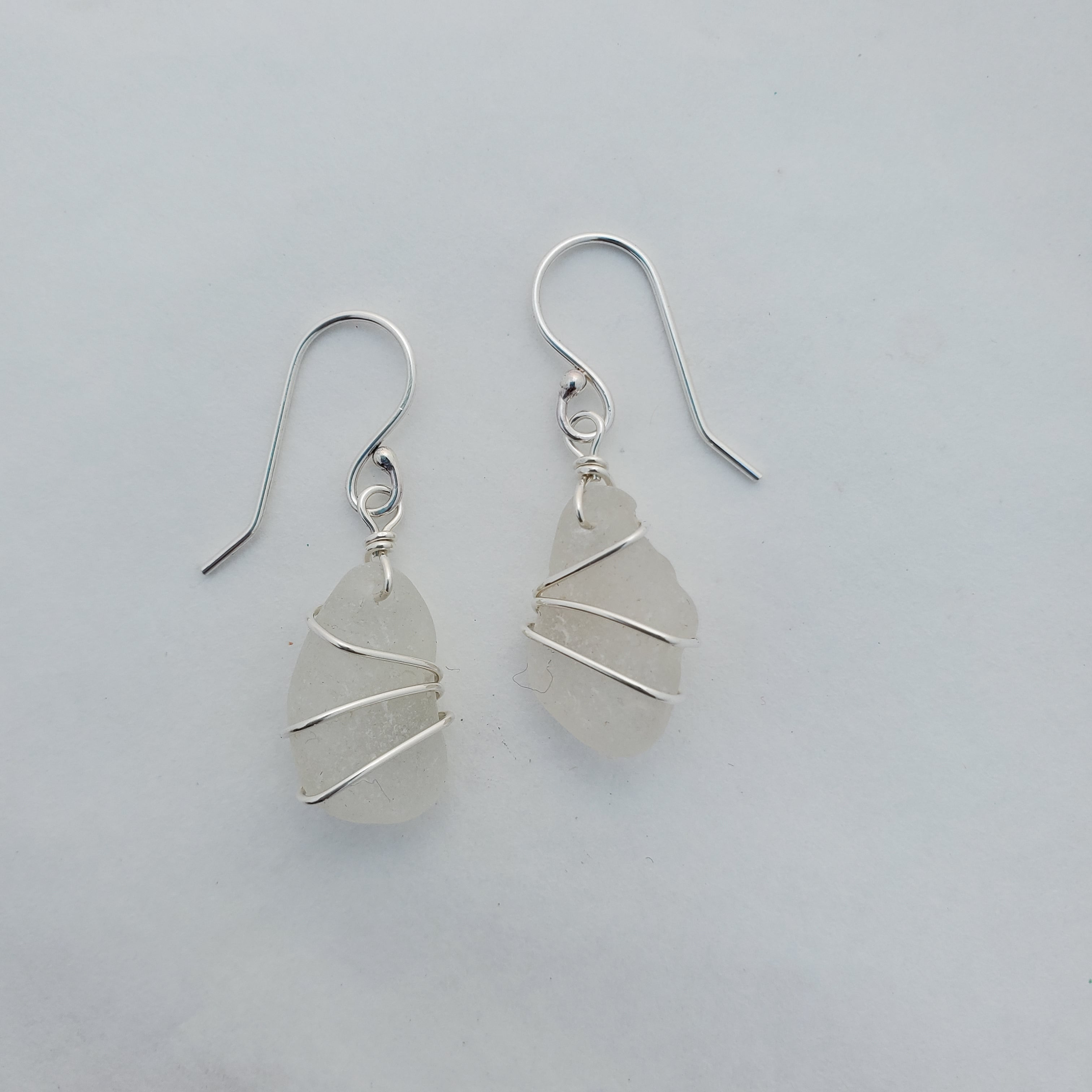 White sea glass earrings wire wrapped in sterling silver with french earring wires on white background