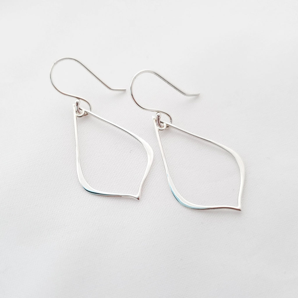 Sterling silver pointed teardrop wire earrings shown laying down.