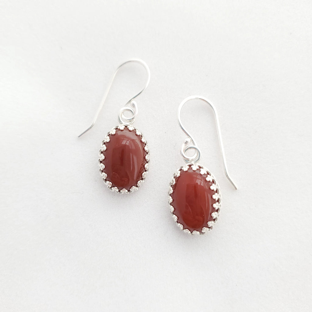 Oval red-orange carnelian gemstones set in sterling silver crown bezel with french earring wires.