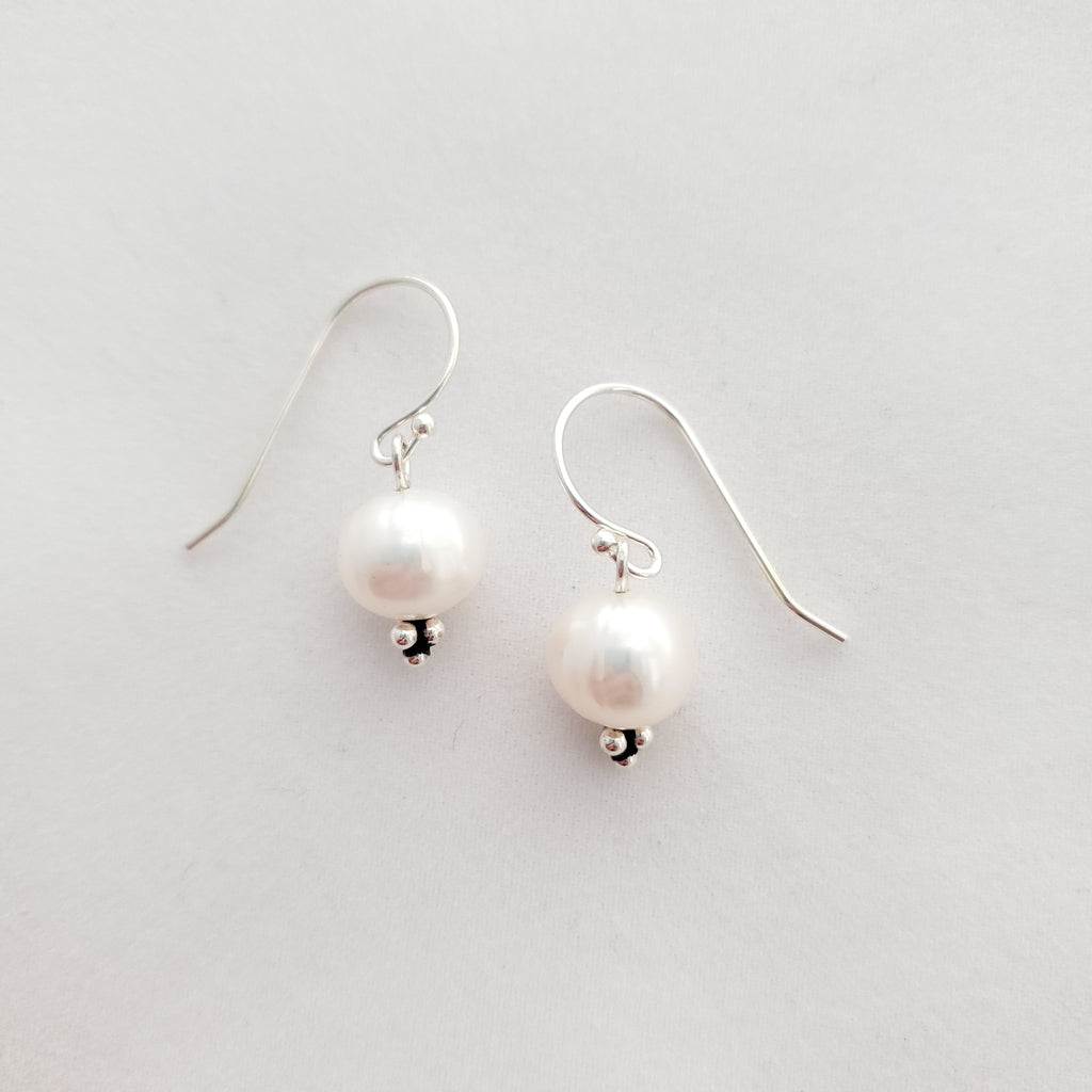 Fresh water pearl dangle earrings with oxidized cluster of small silver balls at bottom for accent.