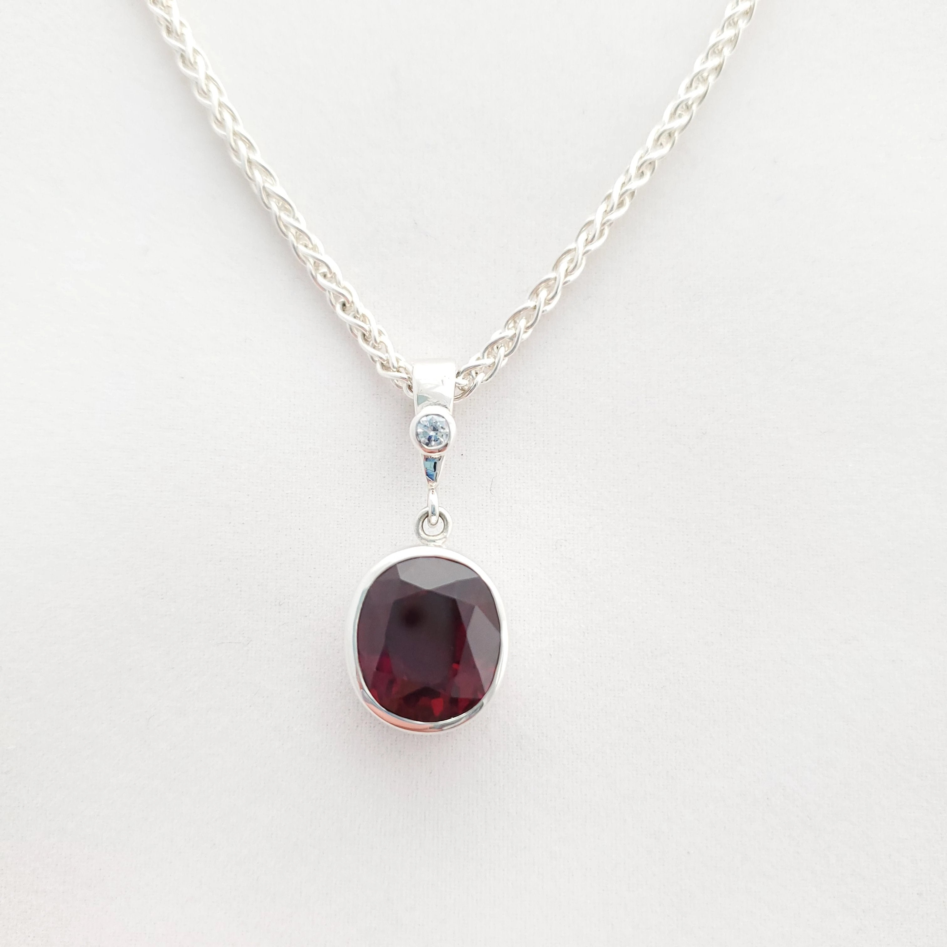 Close up view of faceted dark purple-red garnet bezel set necklace with cz accent
