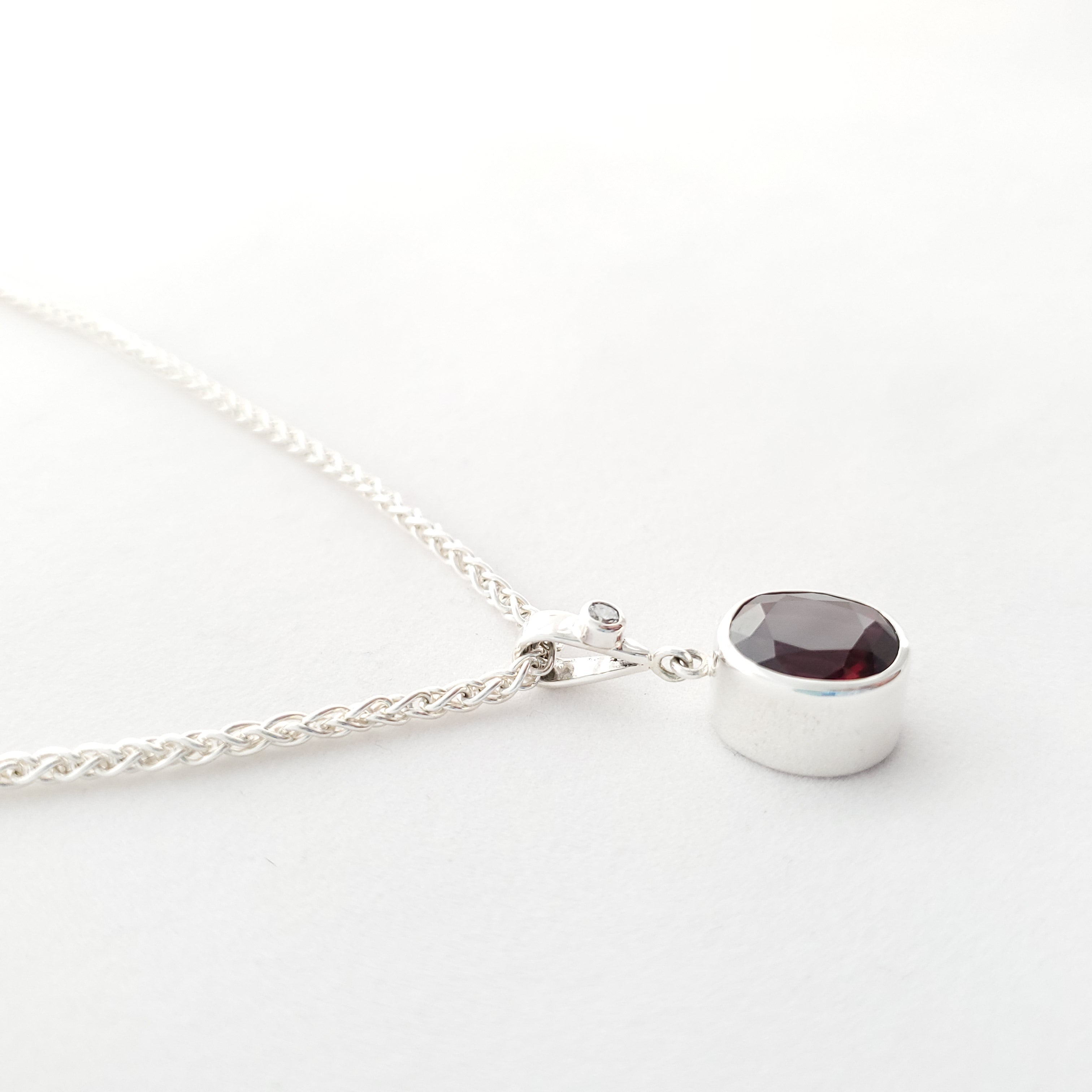 side view of bezel set garnet and cz necklace in sterling silver