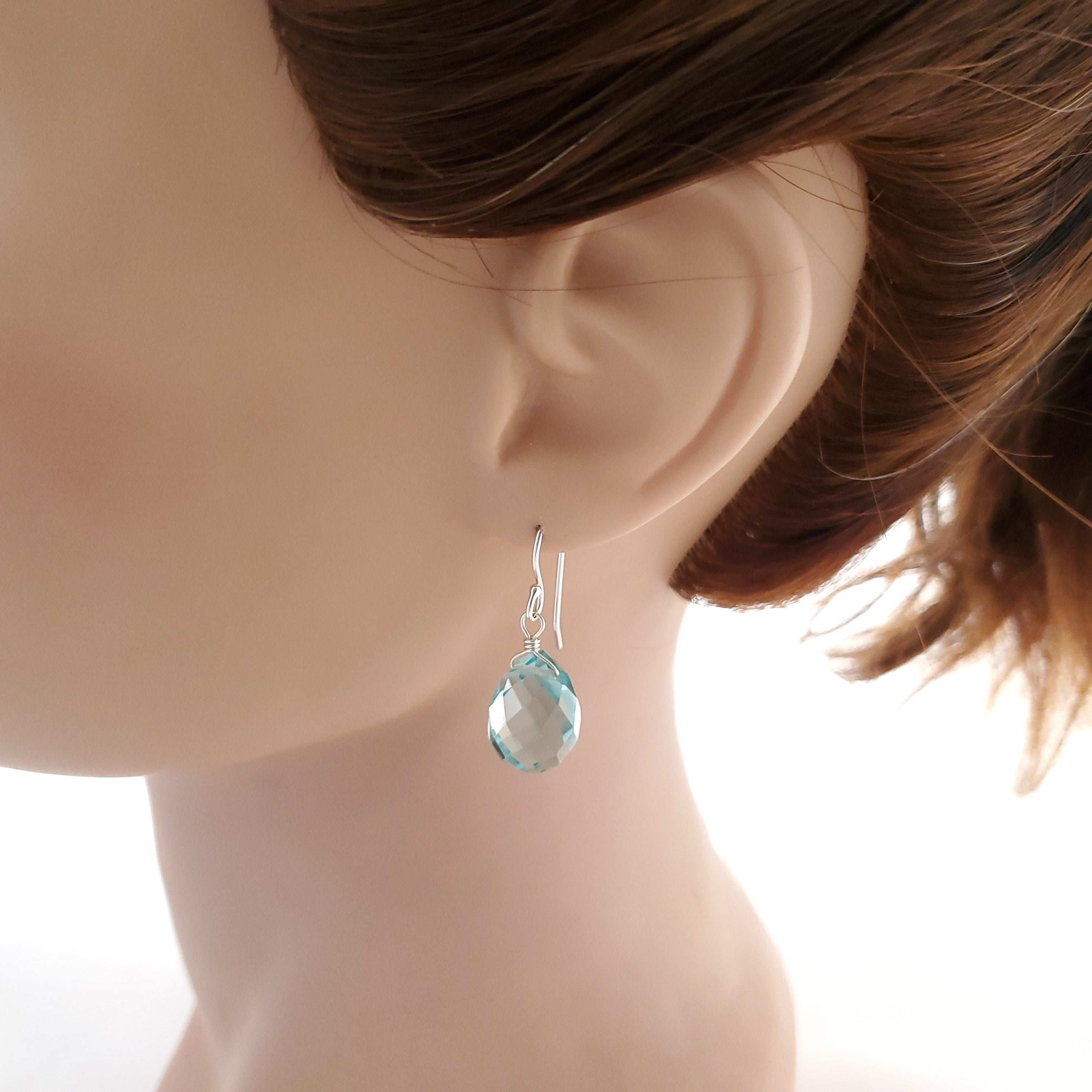 Blue faceted crystal teardrop earrings in sterling silver shown on mannequin