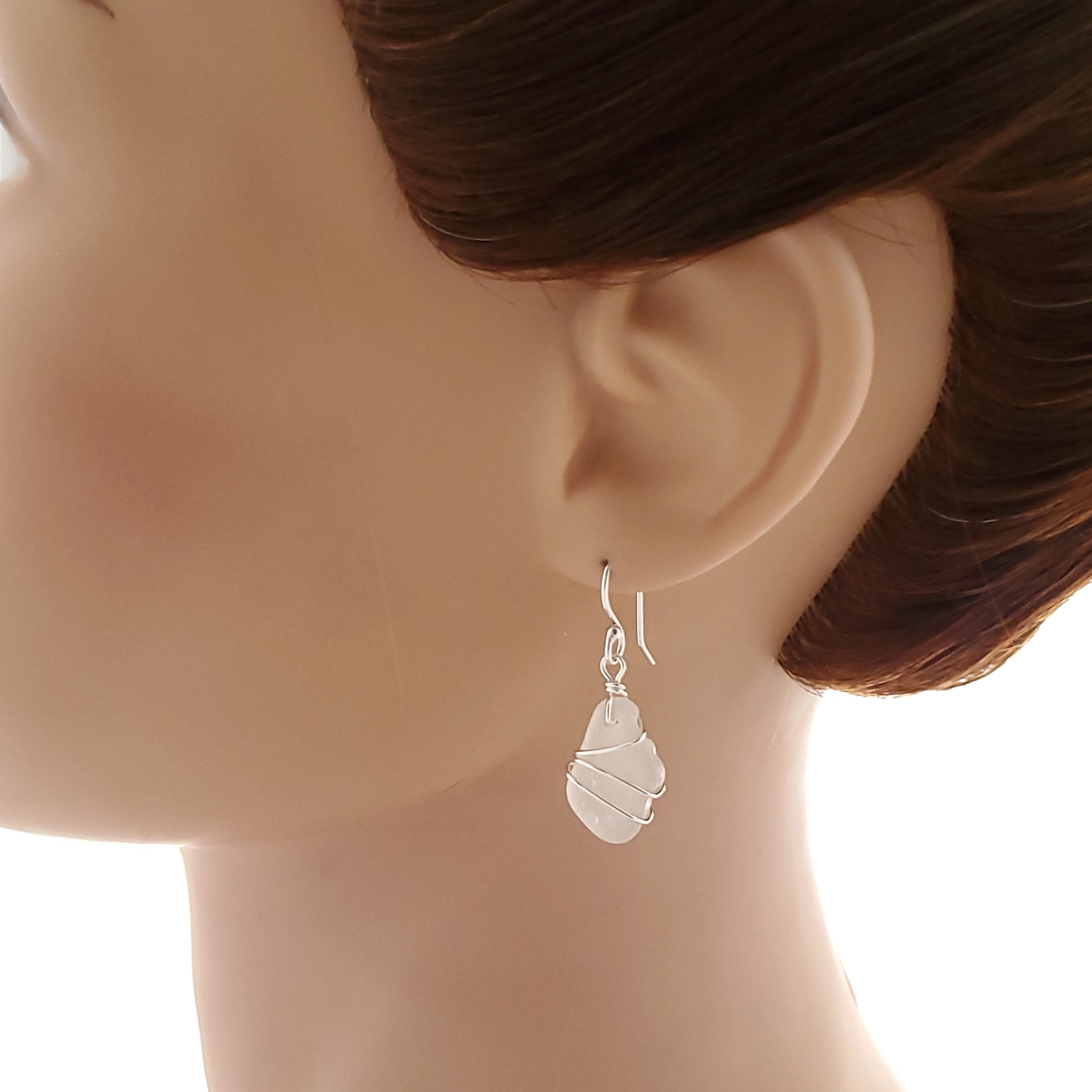 Wire wrapped silver white sea glass earrings shown on mannequin.