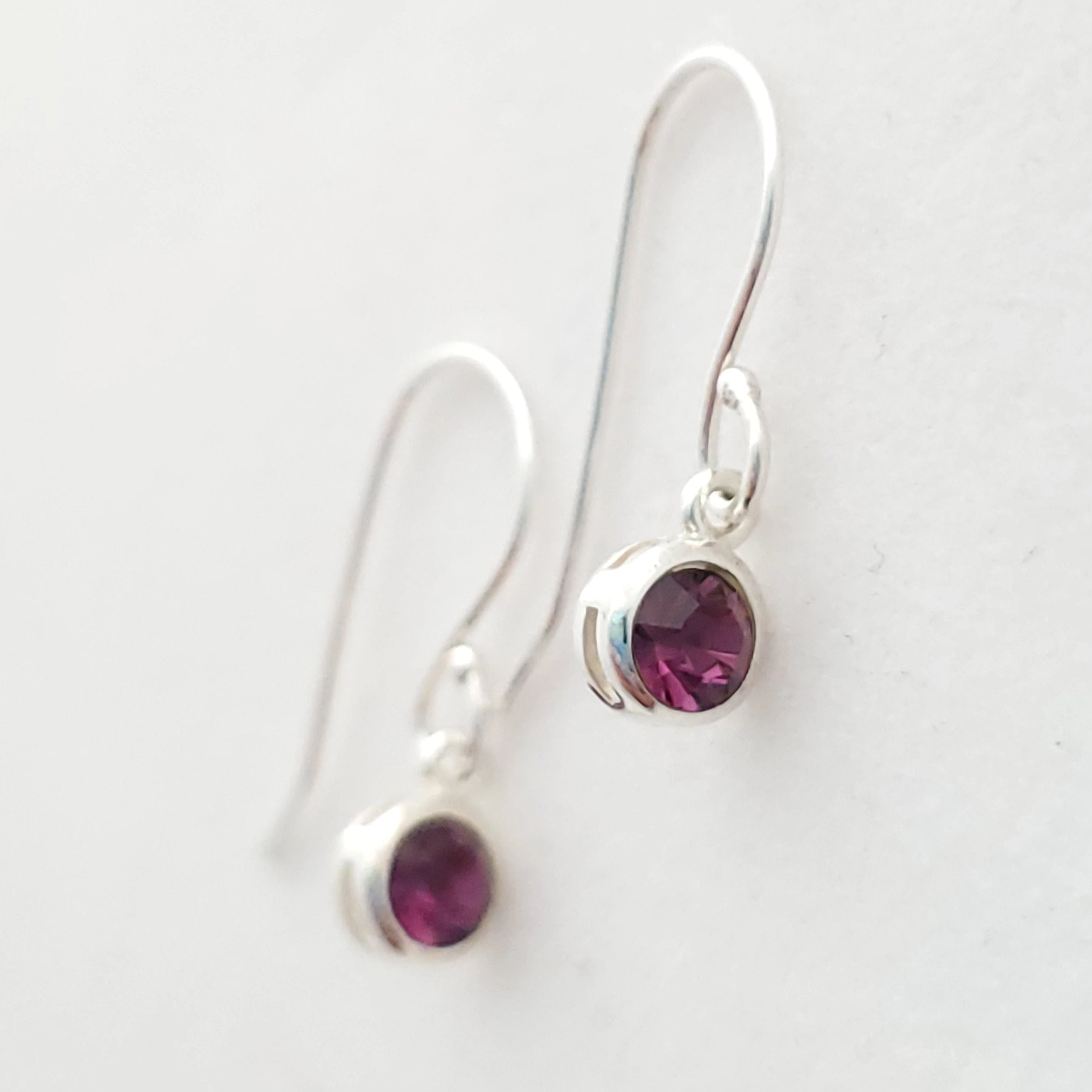 February purple crystal dangle earrings in sterling silver. Laying down side view.