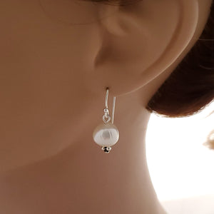 Short fresh water pearl simple dangle earrings shown on mannequin.