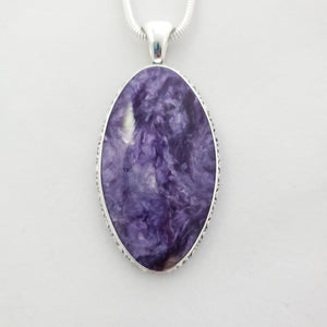 Close up view of large purple bezel set sterling silver pendant.