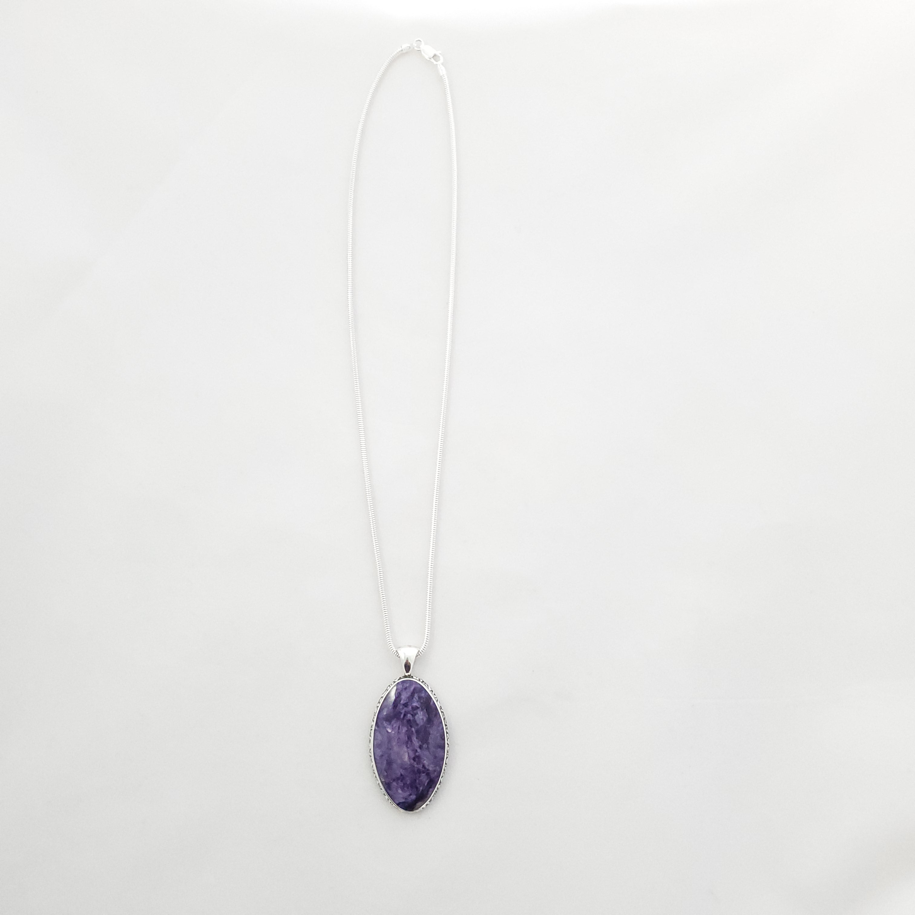 Large purple Charoite pendant on snake chain - face on view.