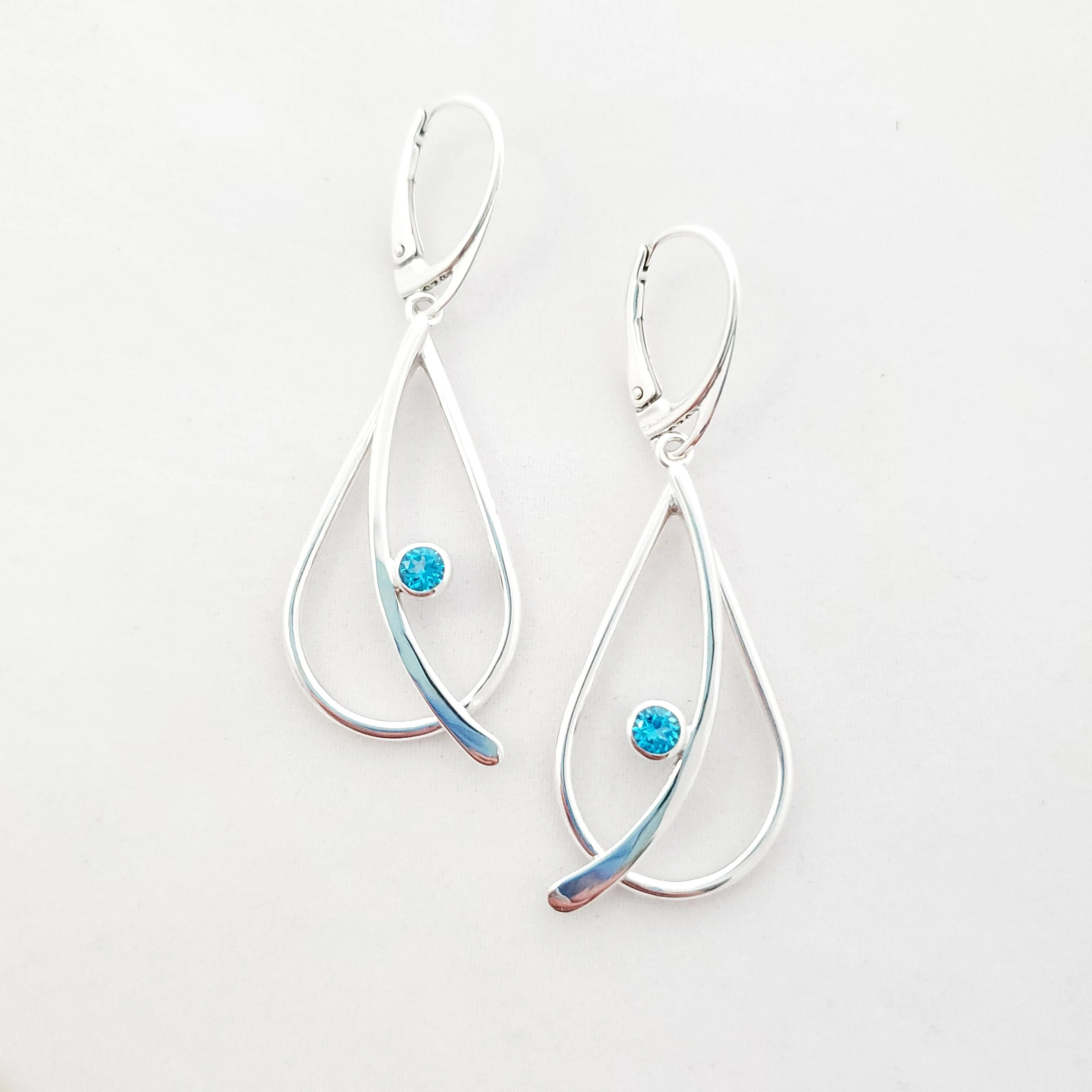 Sterling silver open design teardrop earrings with curved wire attached on top of the teardrop with a small faceted blue topaz bezel set in center. Lever back earring wires.