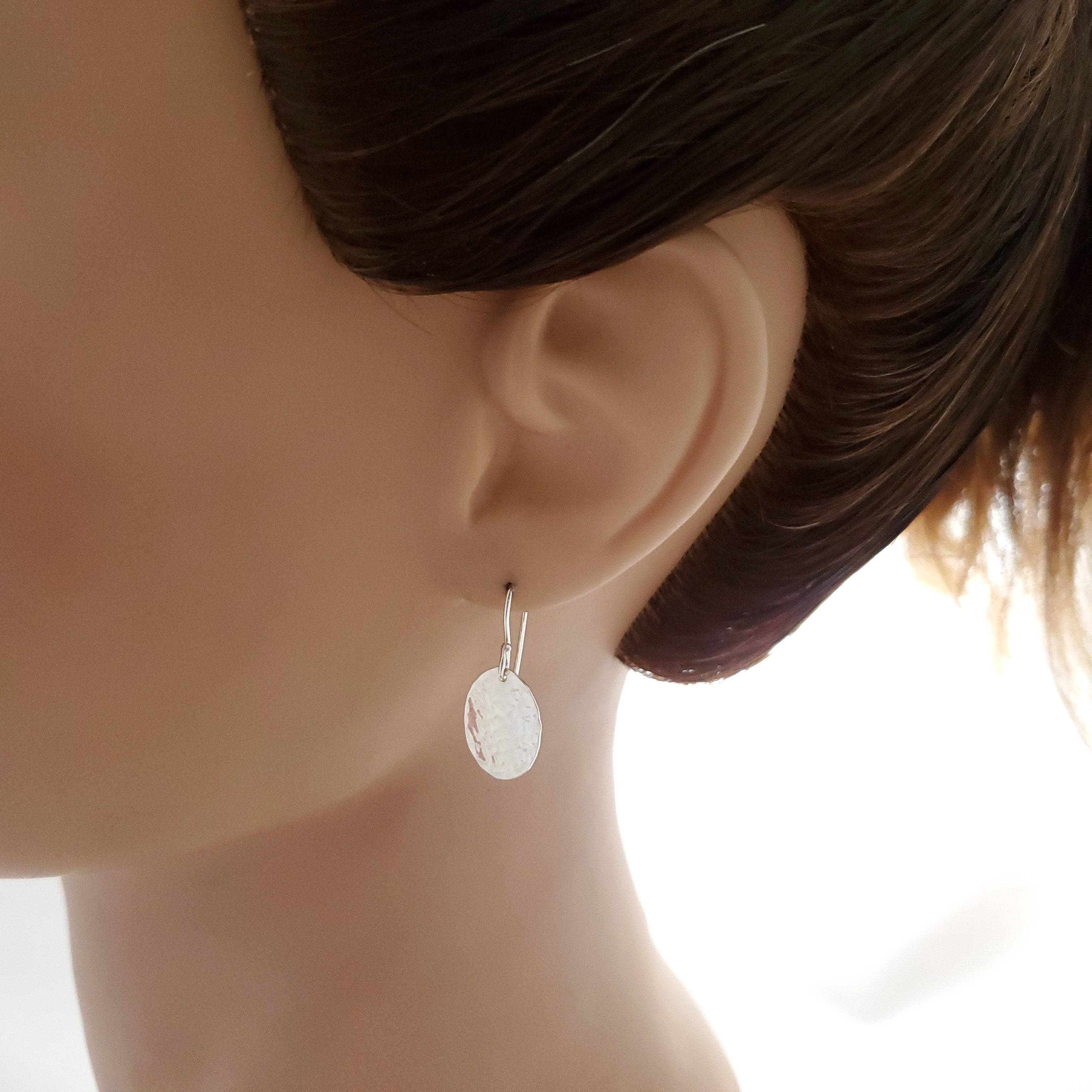 Hammered oval silver earring shown on mannequin