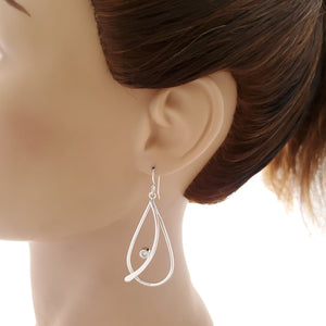 Teardrop silver dangle earring shown on mannequin