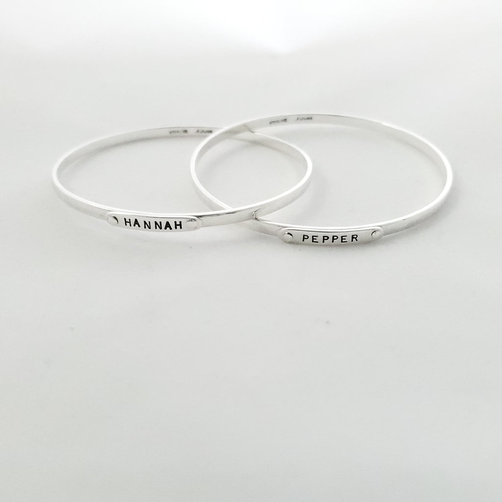 Two silver bangle bracelets shown spread apart but connected. One says HANNAH, the other says PEPPER.