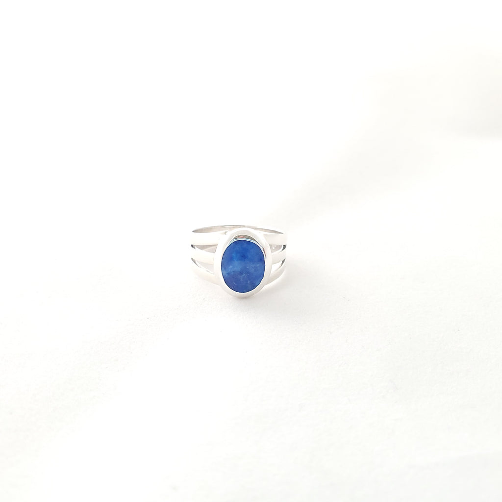 Blue oval sodalite gemstone on silver ring that is solid in the back and opens into three open sections at the top