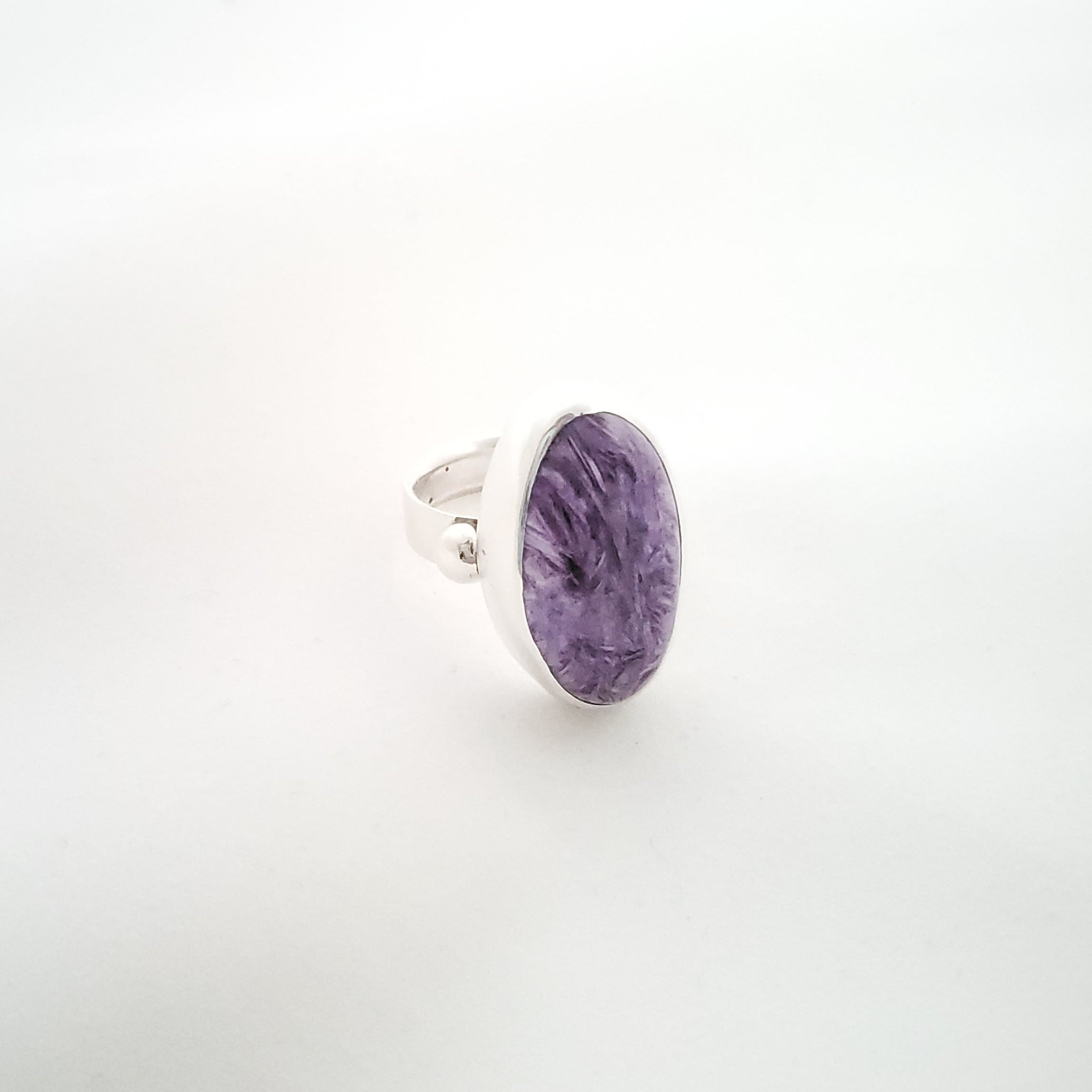 Purple large oval charoite ring shown at side angle