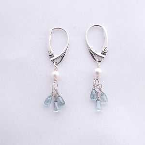 Three small faceted blue zircon teardrop briolettes dangle from one fresh water pearl and hang from lever back earring wires in sterling silver