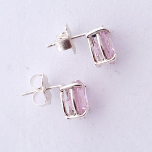 Side view of oval pink faceted post earrings showing basket 4 prong setting