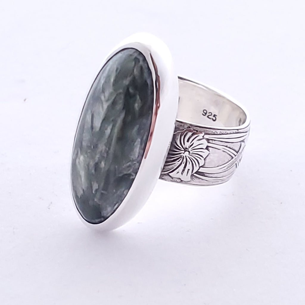 Wide silver band with floral pattern and a thin oval Seraphinite bezel set on top.