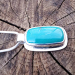 Rectangle shaped turquoise pendant bezel set with tube bail and silver border that is textured with horizontal lines