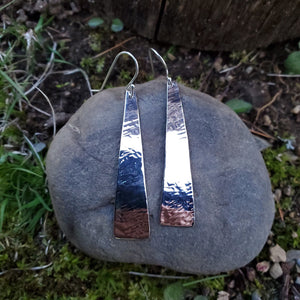 Hammered rectangle tapered earrings displayed on rock