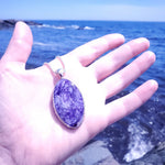 Charoite and sterling silver necklace being held by a hand