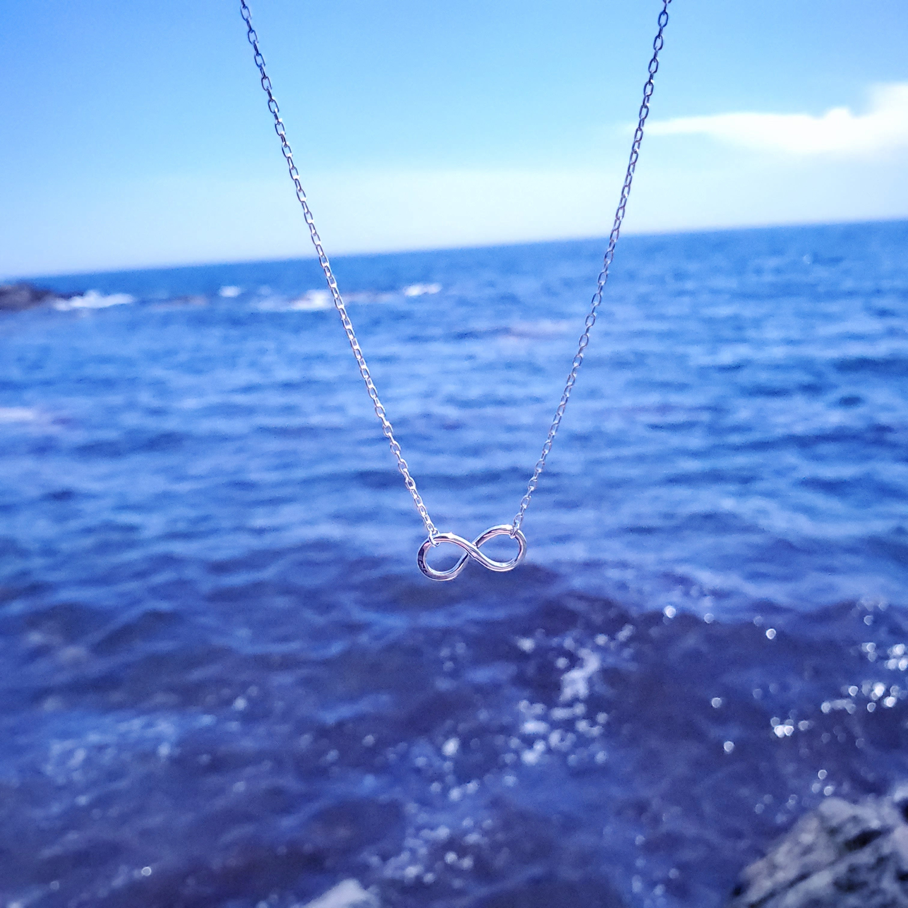 Silver infinity necklace hanging with ocean in background