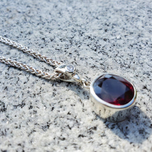 Faceted oval garnet bezel set in sterling silver with cubic zirconia accent on bail. Hanging on woven silver chain.