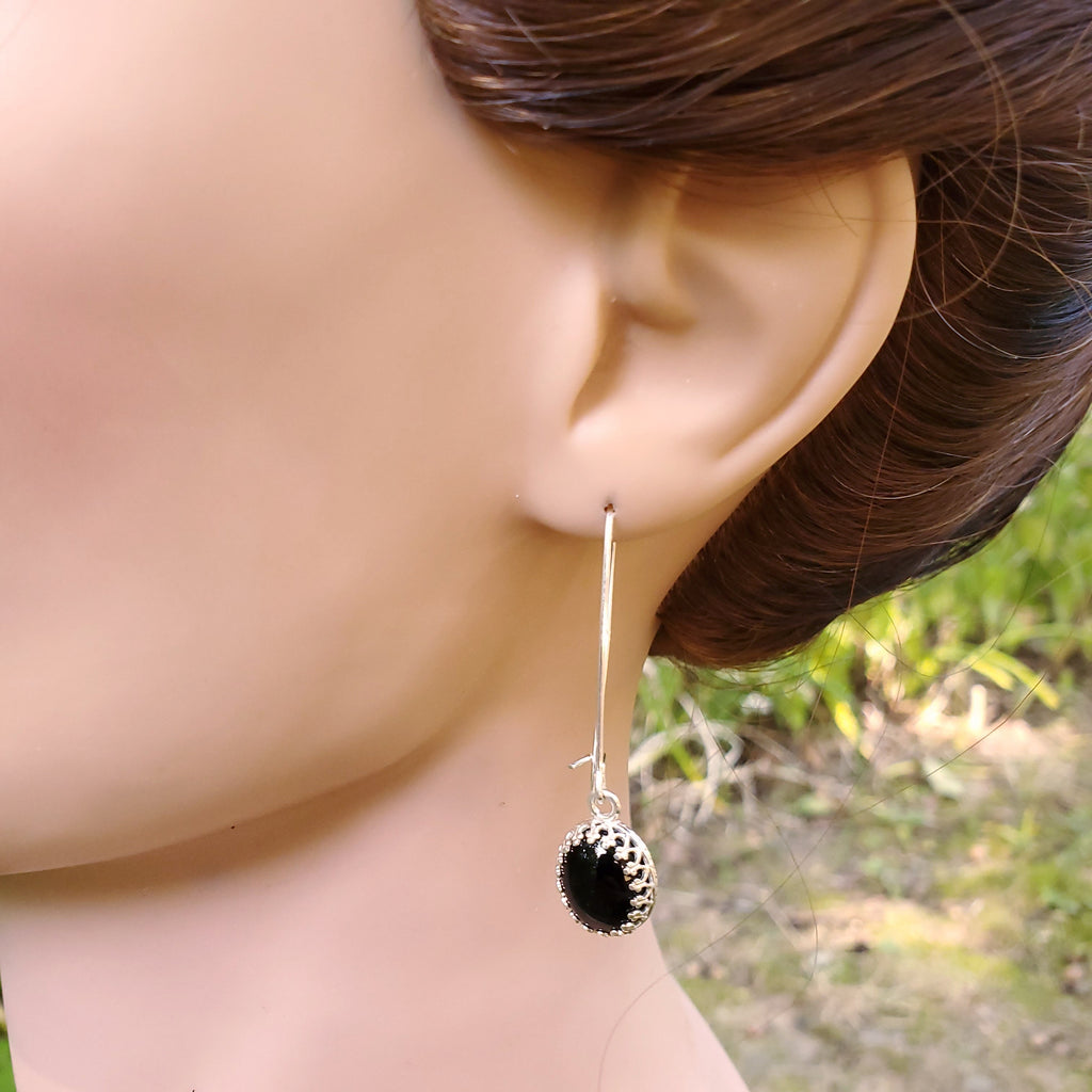 black onyx long dangle earrings displayed on mannequin