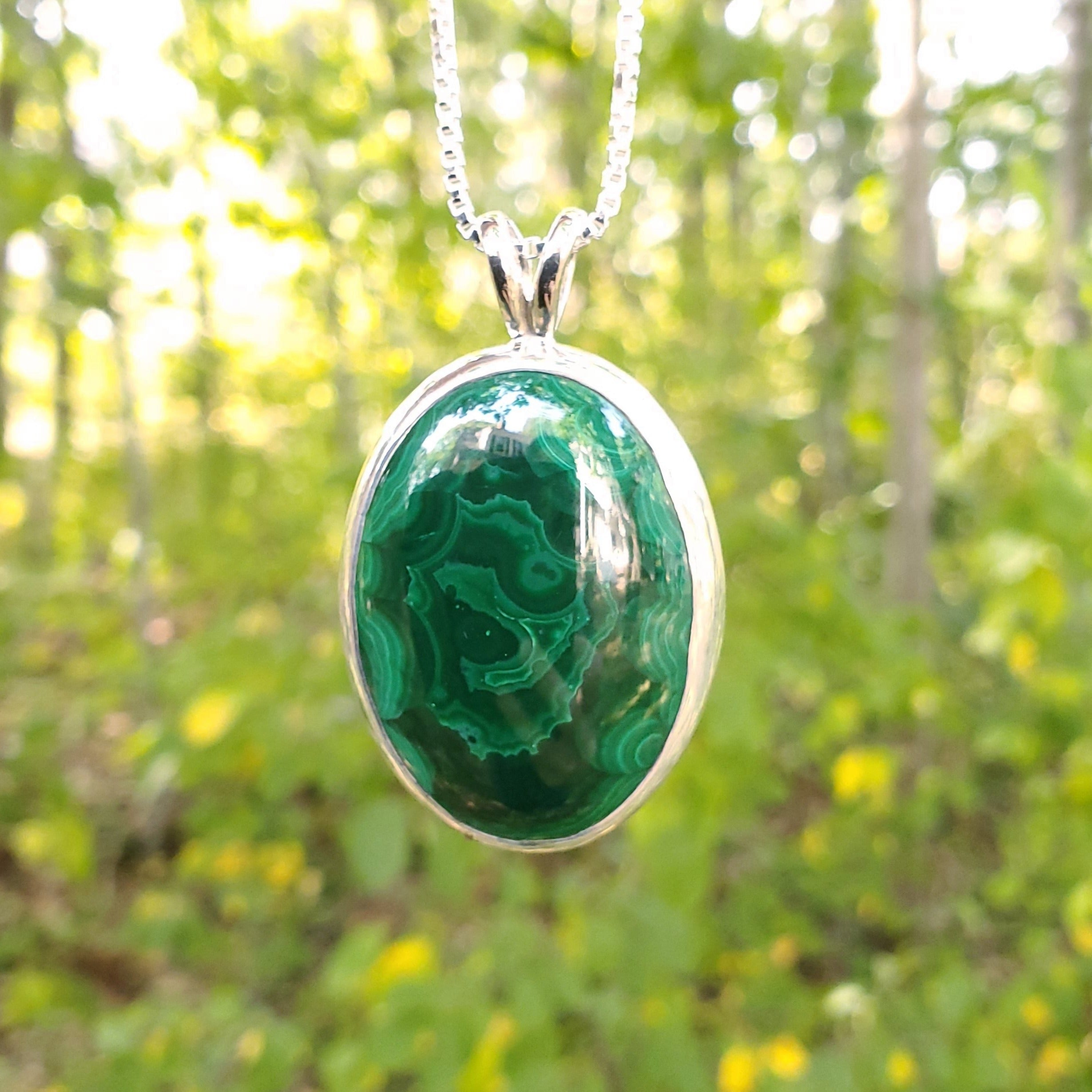 Malachite and silver bezel set necklace with trees in background