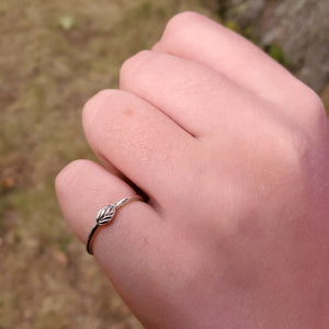Thin silver ring with small silver leaf on top sitting horizontally