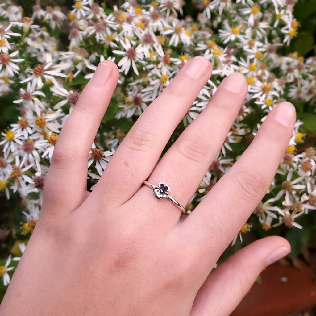 Silver flower ring displayed on hand with flowers in background