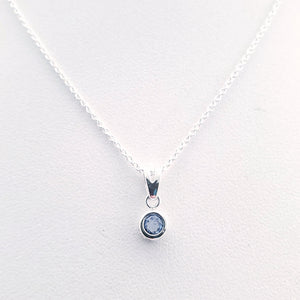 Light blue round faceted stone in silver necklace