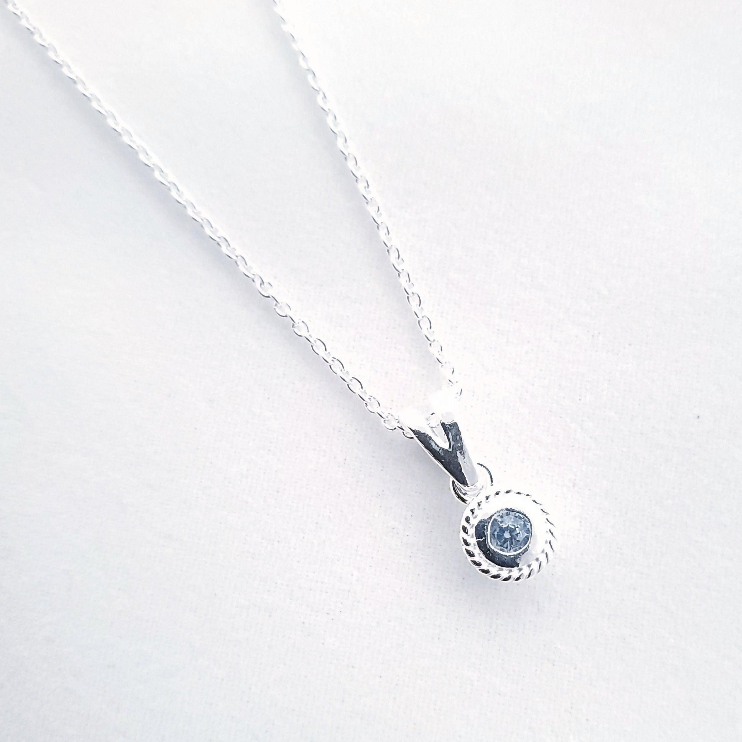 Light blue faceted round stone in silver necklace
