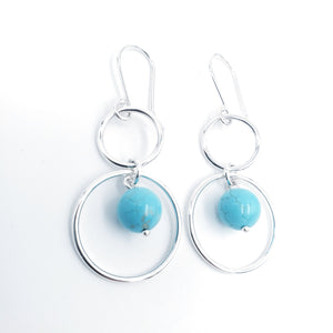 two silver circles of different sizes are linked together with a turquoise bead hanging in lower circle