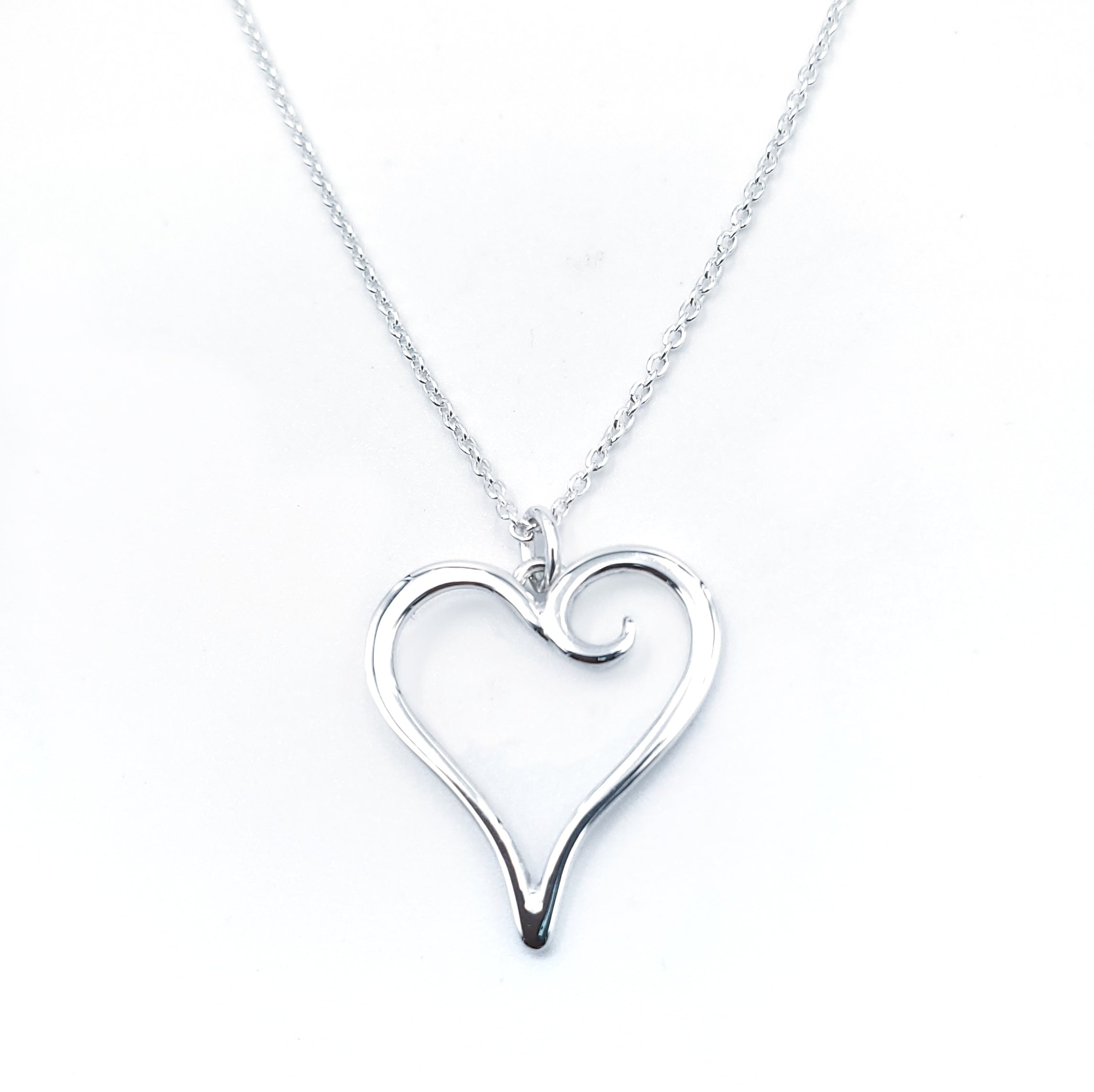 Silver heart with spiral on one side