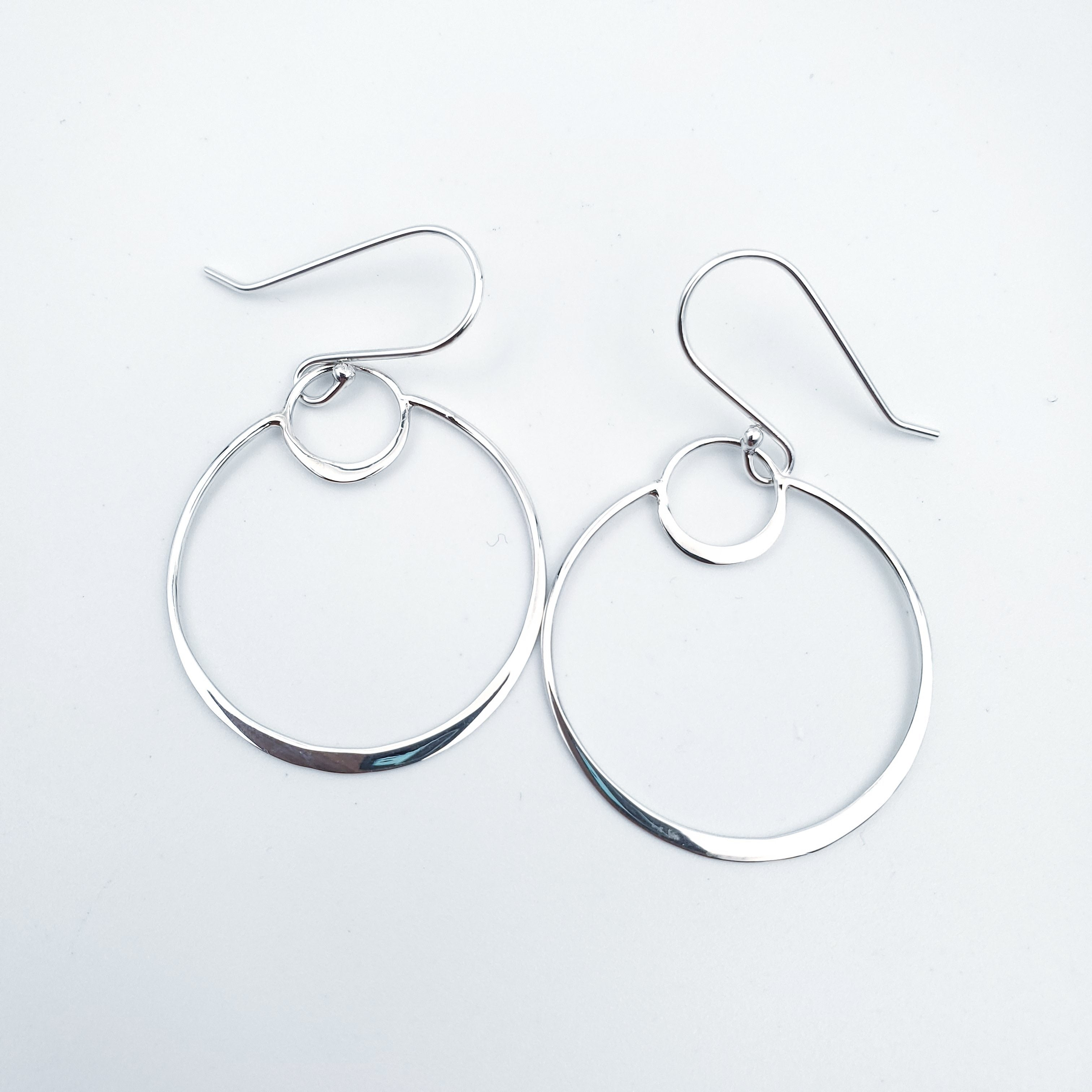 Small silver circle inside larger silver silver eclipse silver earrings