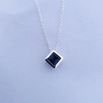 Square sapphire pendant with chain going through setting