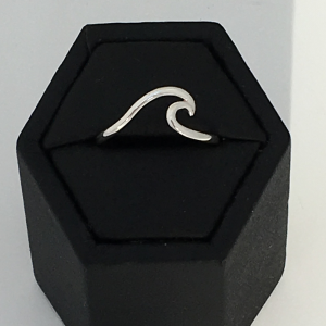 Sterling silver ring with a wave on the top dispalyed in black hexagon ring display