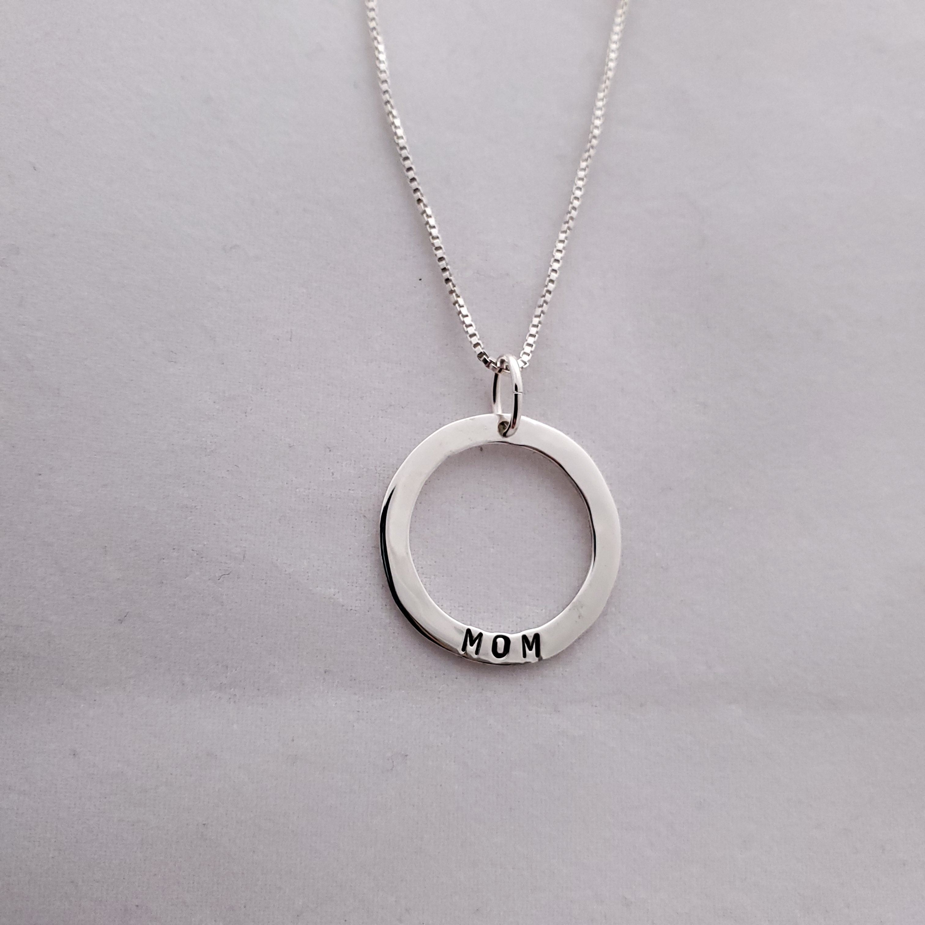 Silver circle necklace with MOM stamped on bottom of circle, hanging on chain