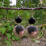Round flat black onyx beads are attached with loops to large textured silver discs to create these statement earrings