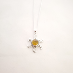 Amber bezel set pendant with silver open sun rays extending from stone.