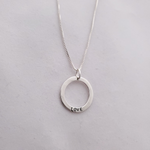 Silver circle necklace with LOVE stamped on bottom of circle, hanging on chain