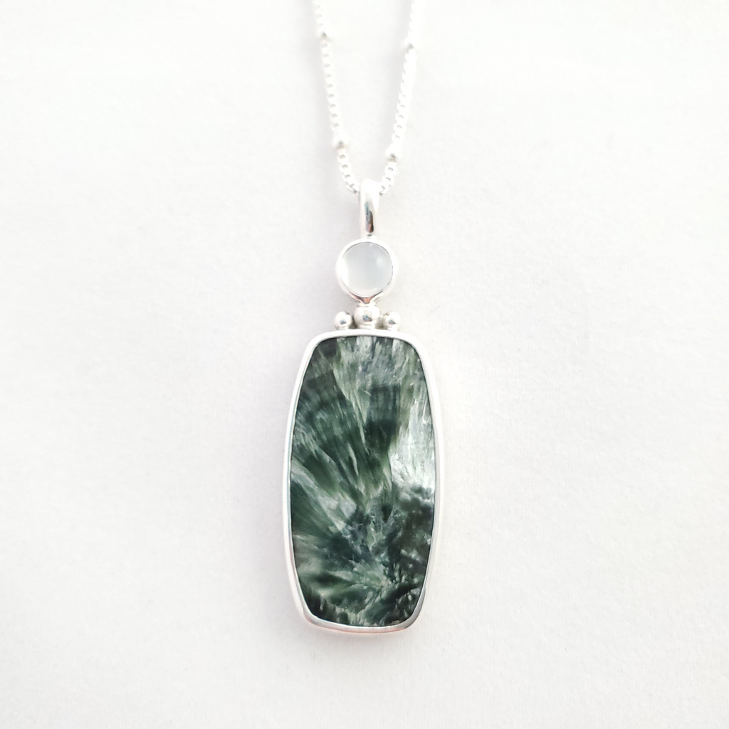 This necklace features a rectangular shaped green seraphinite gemstone bezel set with three silver balls on top and a small round bezel set moonstone above the balls.